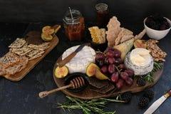 Cheeseboard con vari formaggi, cracker, frutta, miele, ramoscelli dei rosmarini e chutney fotografie stock