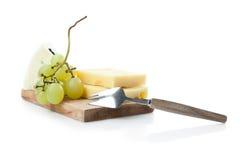 Cheeseboard di formaggio a pasta dura e blu con l'uva Fotografia Stock