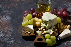 Cheeseboard, fresh fruits and honey on a dark background. Top view, horizontal Royalty Free Stock Photography