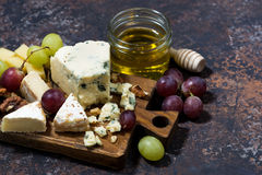 Cheeseboard, fresh fruits and honey on a dark background. Closeup Royalty Free Stock Image