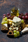 Cheeseboard, fresh fruits and honey on a dark background. Top view Stock Images