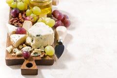 Cheeseboard, fresh fruits, honey and white background. Closeup Stock Photo