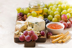 Cheeseboard, fresh grapes and honey on a white background. Horizontal Stock Photography