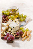 Cheeseboard, fresh grapes and honey on a white background. Top view Royalty Free Stock Photos