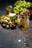 Cheeseboard, fruit and glass of white wine on a dark background. Vertical, closeup Stock Photo