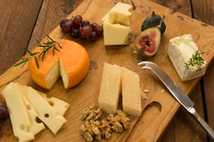Cheeseboard with fruit and herbs Stock Photos