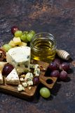Cheeseboard, fruits and honey on a dark background, vertical. Cheeseboard, fruits and honey on a dark background, top view Royalty Free Stock Image