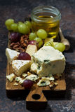 Cheeseboard, fruits and honey on a dark background, vertical. Top view Stock Image
