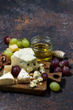 Cheeseboard, fruits and honey and dark background, vertical. Top view Royalty Free Stock Images