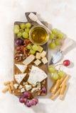 Cheeseboard, frutti e miele su un fondo bianco, verticale immagini stock
