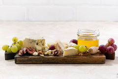 Cheeseboard, grapes and honey on a white background. Closeup Royalty Free Stock Photography
