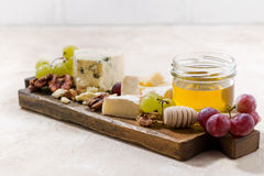 Cheeseboard, grapes and honey on a white background. Selective focus, horizontal Royalty Free Stock Photos