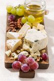 Cheeseboard, grapes and honey on a white background, vertical. Cheeseboard, grapes and honey on a white background, closeup Royalty Free Stock Photography