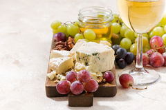 Cheeseboard, grapes and wine on a white background. Closeup Stock Image