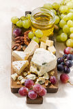 Cheeseboard, grapes and wine on a white background, vertical. Cheeseboard, grapes and wine on a white background, top view Royalty Free Stock Photo