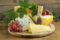 Cheeseboard (Maasdam, Roquefort, Camembert) and grapes Stock Images