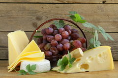 Cheeseboard (Maasdam, Roquefort, Camembert) and grapes Stock Photography