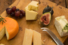 Cheeseboard med frukt och örter Arkivfoton