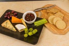 Cheeseboard-Servierplatte mit Trauben und Essiggurke und Cracker stockbild