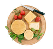 Cheeseboard with tomatoes, herb basil, isolated on white. Stock Photos