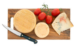 Cheeseboard with tomatoes and knife. Artisan cheese. Isolated. Royalty Free Stock Photo