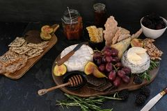 Cheeseboard with a variety of cheeses, crackers, fruit, honey, rosemary sprigs and chutney. Festive cheeseboard with a variety of cheeses including brie and Stock Photos
