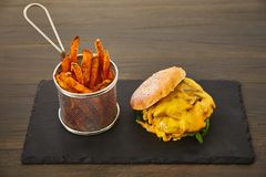 Cheeseburger με ένα κυλημένο επάνω κουλούρι με το σουσάμι, το λειωμένο κίτρινο τυρί, η πράσινη φρέσκια σαλάτα και η φρέσκια μπριζ Στοκ φωτογραφίες με δικαίωμα ελεύθερης χρήσης