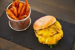 Cheeseburger με ένα κυλημένο επάνω κουλούρι με το σουσάμι, το λειωμένο κίτρινο τυρί, η πράσινη φρέσκια σαλάτα και η φρέσκια μπριζ Στοκ εικόνα με δικαίωμα ελεύθερης χρήσης