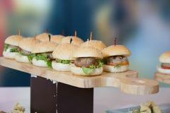 Cheeseburger ολισθαίνοντες ρυθμιστές με την ντομάτα μαρουλιού Στοκ Εικόνες