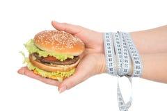 Cheeseburger бургера в руках с лентой измерения Стоковая Фотография RF