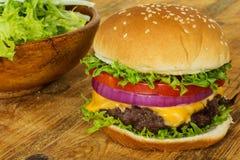 Cheeseburger/гамбургер на деревенской древесине Стоковое Изображение