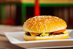 Cheeseburger крупного плана свежий на белой плите на запачканной предпосылке Стоковое Изображение RF