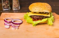 Cheeseburger с свежими отбензиниваниями на деревянной доске Стоковое Изображение