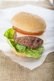 Cheeseburger americano classico dell'hamburger casalingo gigante sul sacco Immagini Stock Libere da Diritti