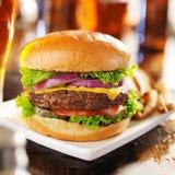 Cheeseburger avec de la bière et des pommes frites Photos libres de droits