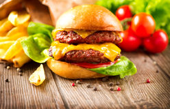 Cheeseburger avec de la salade et les pommes frites fraîches Image libre de droits