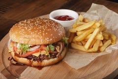 Cheeseburger avec des pommes frites Images libres de droits