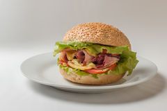 Cheeseburger avec du jambon, la tomate et la salade photo stock