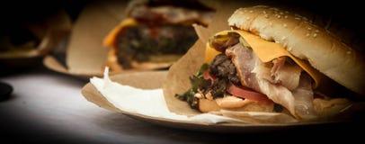 Cheeseburger avec le lard, la viande, les tomates et la salade sur un fond foncé images stock