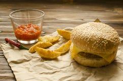 Cheeseburger avec les pommes de terre et la sauce chili frites sur une PA de métier images stock
