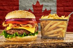 Cheeseburger with bacon. Canada flag`s in background. Cheeseburger with bacon. Canada flag`s on brick wall in background stock photos