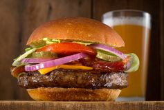 Cheeseburger with Bacon. A juicy delicious cheeseburger with bacon, lettuce, tomato, red onions and pickle with a glass of beer Stock Photography