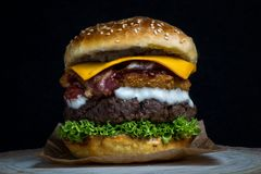 Cheeseburger with bacon, lettuce, cheddar, onion rings and mayonnaise royalty free stock images