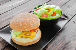 Cheeseburger with bacon and tartar sauce and garden salad Stock Photo