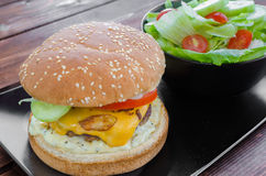 Cheeseburger with bacon and tartar sauce and garden salad Stock Image