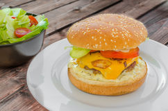 Cheeseburger with bacon and tartar sauce and garden salad Royalty Free Stock Photography
