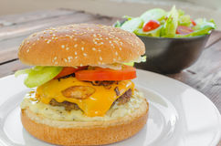 Cheeseburger with bacon and tartar sauce and garden salad Royalty Free Stock Image