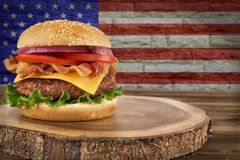 Cheeseburger with bacon, tomato, onion and lettuce. Cheeseburger with bacon on wooden plank. USA flag`s on brick wall in background stock images