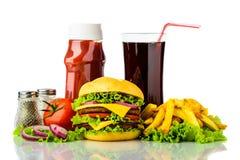 Cheeseburger, batatas fritas, bebida e ketchup Imagem de Stock