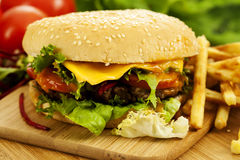 Cheeseburger on the board with french fries Royalty Free Stock Images